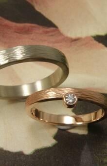 * roodgouden ring met spitse hamerslag met 0,05 crt briljant geslepen diamant aan de zijkant gezet  * witgouden ring met spitse hamerslag  * trouwringen uit het Oogst atelier