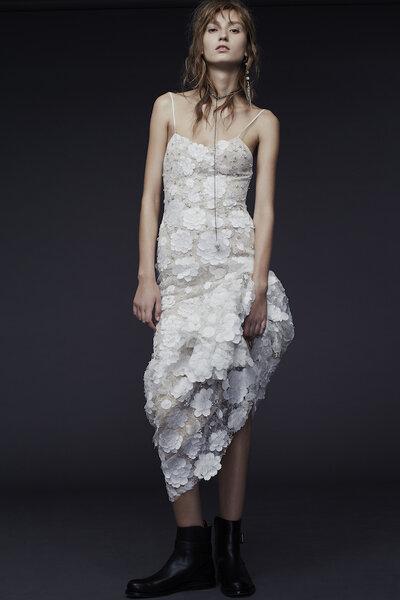 Vestido de novia en color marfil con silueta ceñida, encaje chantilly, motivos florales en relieve y delicados tirantes