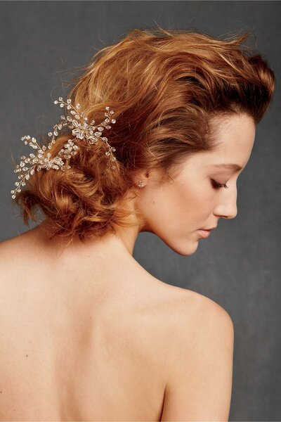 Lässig gewellter Haarknoten im Nacken mit edlem Haarschmuck verziert.