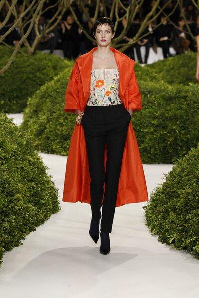 Conjunto para fiesta con pantalones estilo cigarrette en color negro, top con detalles de flores multicolor y capa en tono rojo con mangas anchas