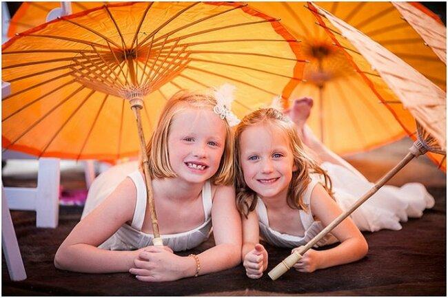 Mädchen mit orange Sonnenschirmen.
