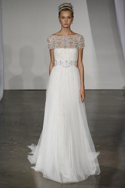 Vestido de novia corte tradicional y sencillo con escote ilusión, mangas cortas y destalle de pedrería en la cintura