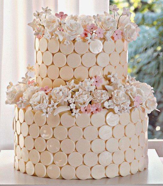 Bolo rosé pálido com adorno em flores e acabamento de mini círculos.