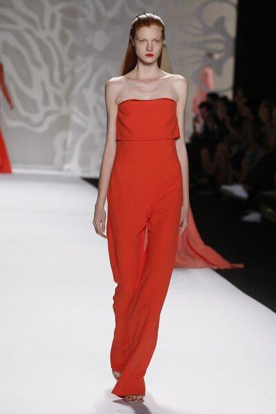 Enterizo en color anaranjado intenso con escote strapless, cauda pequeña y pantalones de corte recto