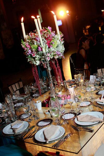 Decoración de mesa de banquete con gran centro de mesa floral y velas altas.