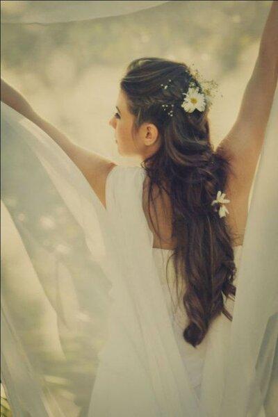 Vestido de noiva soltinho com detalhe nas costas e cabelos soltos com flores. Foto: Alba Martins