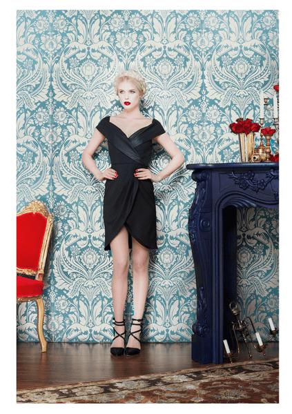 Vestido de fiesta corto con escote de marco y mangas cortas en color negro, acabado en satén y asimétrico