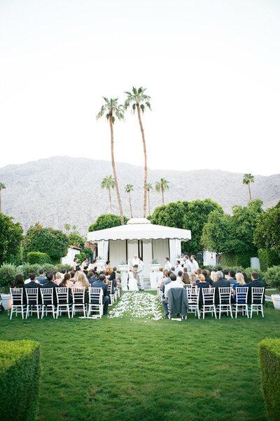 Ao ar livre, uma tenda branca, com uma paisagem tropical. Foto: Lane Dittoe