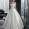 Robe de mariée coupe princesse ceintrée à manches courtes transparentes et ornée de pierreries.