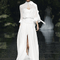 Vestido de novia con cuello cerrado, escote ilusión, mangas largas holgadas y abertura al frente en la falda