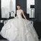Robe de mariée coupe princesse avec jupe volumineuse aux mouvements structurés.