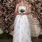 Vestido de noiva com corte princesa com decote cai-cai e detalhes bordados em verde.