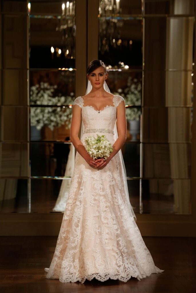 Vestido de novia cubierto con encaje y mangas cortas , acompañado de un cinturón de pedrería y un velo vals - Foto Romona Keveza