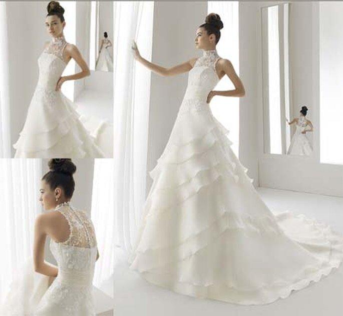 Vestido de novia con medio talle cubierto en encaje, de escote de cuello alto hasta el cuello. Falda con capas superpuestas