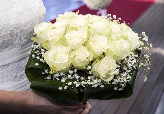 Ramo de rosas blancas combinadas con follaje y flores pequeñas. Foto vía Shutterstock
