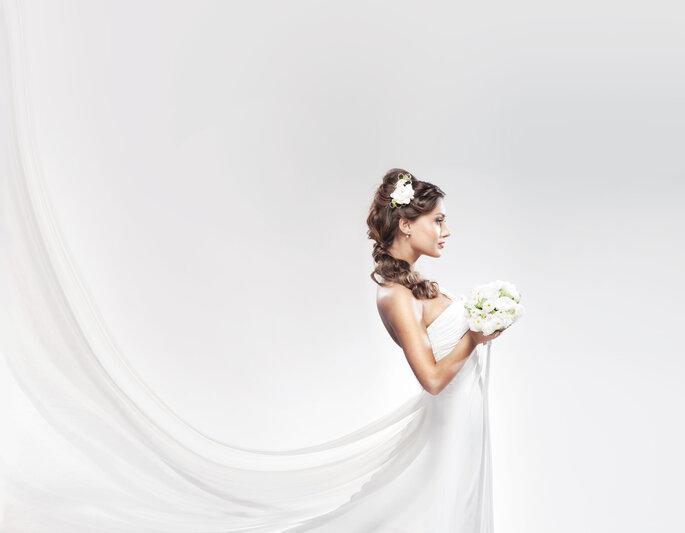 Novia con vestido y bouquet blanco. Foto vía Shutterstock