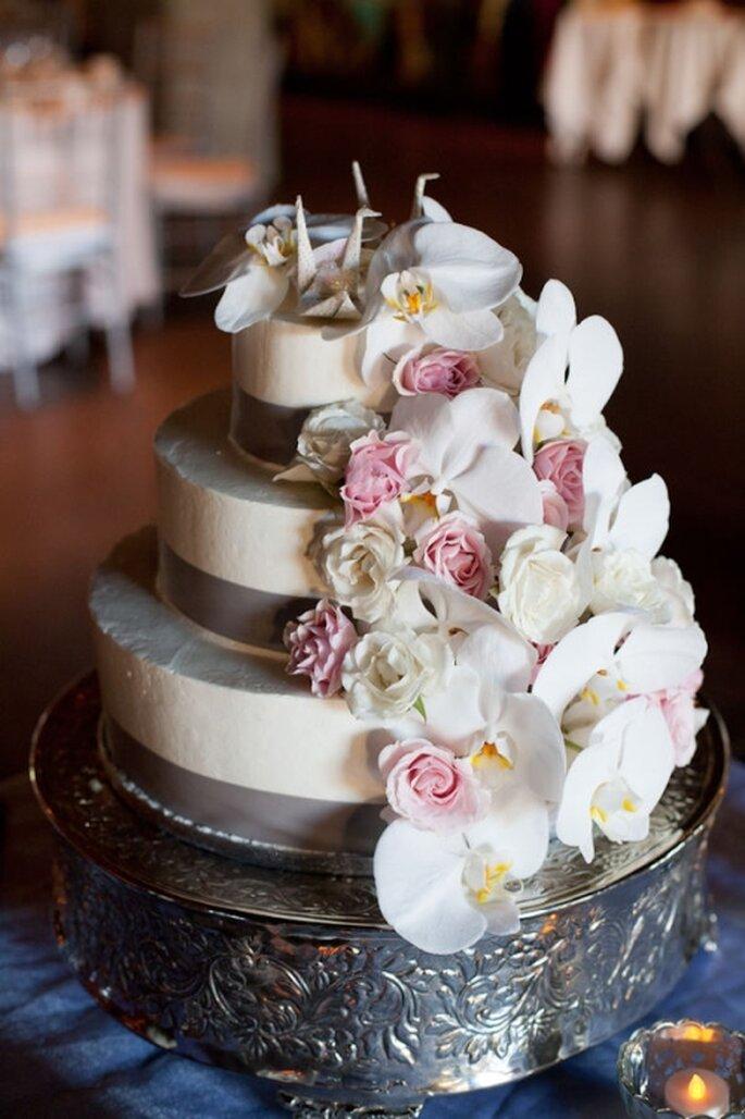 Pastel de boda blanco con gran detalles floral en un lado y decorado con cintilla
