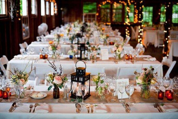 Mesas plagadas de flores naturales y fanales