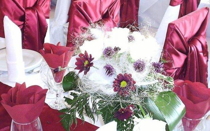 Salone con bouquet di fiori rossi e bianchi e sedie rivestite in stoffa rossa: ideale se l'abito della sposa é a tono