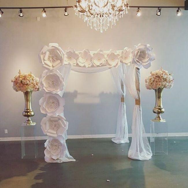 Gazebo de madera decorado con tela y flores gigantes de papel