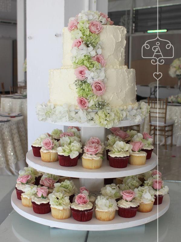 Decoración en crema con flores naturales complementada con cupcakes
