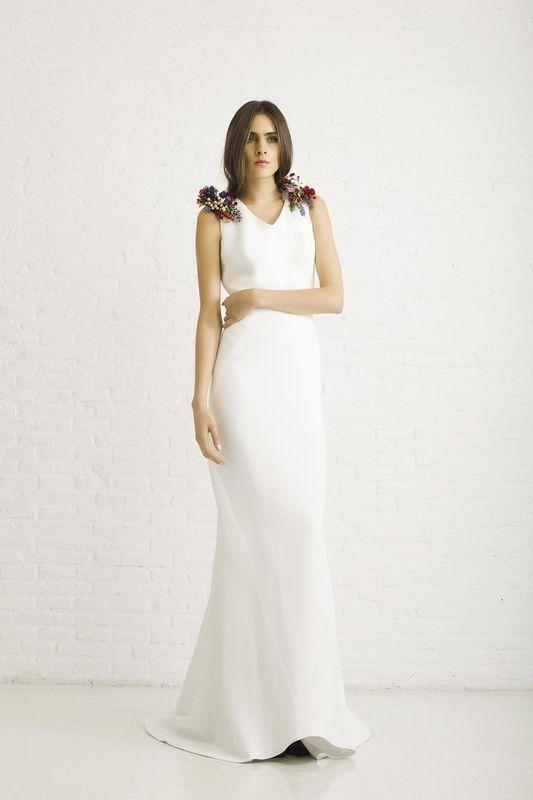 SASHA CON ADORNOS. Vestido de novia realizado en crepe mate de seda con cortes longitudinales y flores de colores en los hombros.