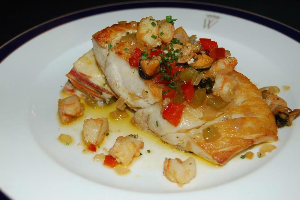 Lomo de pargo a la parrilla con salpicón caliente de mariscos y verduras.