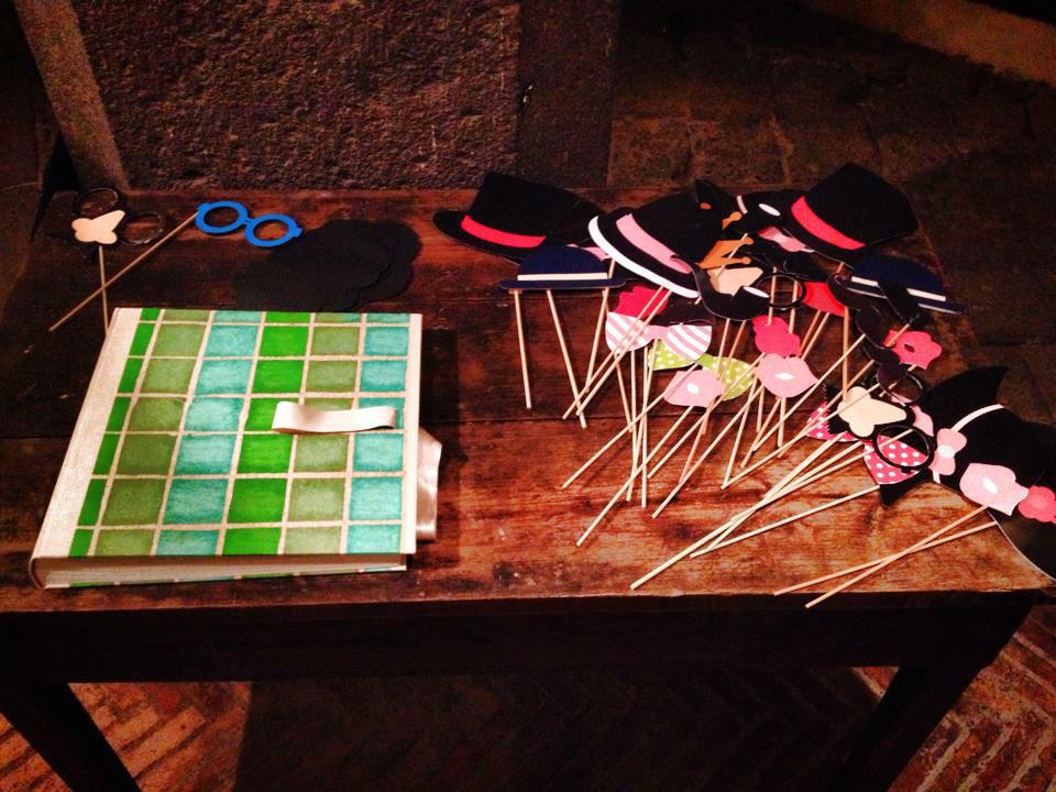 Photobooth di Alessandro Zingone - Foto naturali di matrimonio: servizi fotografici e cabina photobooth. Alcune maschere tipo bastoncino e l' album per gli sposi.
