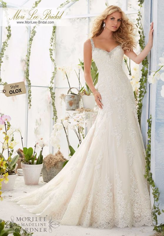"""Dress Style OLOX Embroidered Edging With Crystal Beading Meets The Alencon Lace Appliques And Scalloped Hemline On The Net Gown  Available in Three Lengths: 55"""", 58"""", 61"""". Colors available: White/Silver, Ivory/Silver, Light Gold/Silver."""