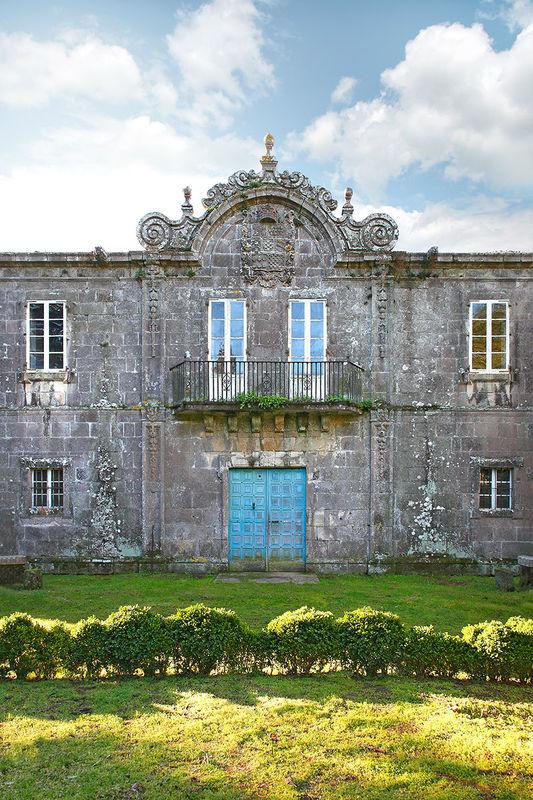 Detalle de la puerta principal con su balcón, y el escudo nobiliario enmarcado en el frontón barroco