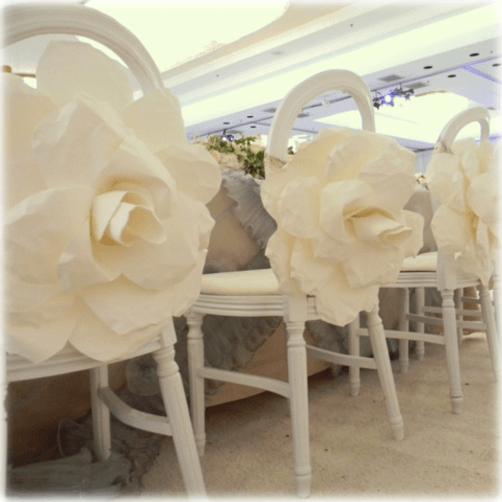 Decoración de sillas de invitados con flores gigantes