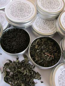 Finas hojas de té de Verde en cajitas metálicas.