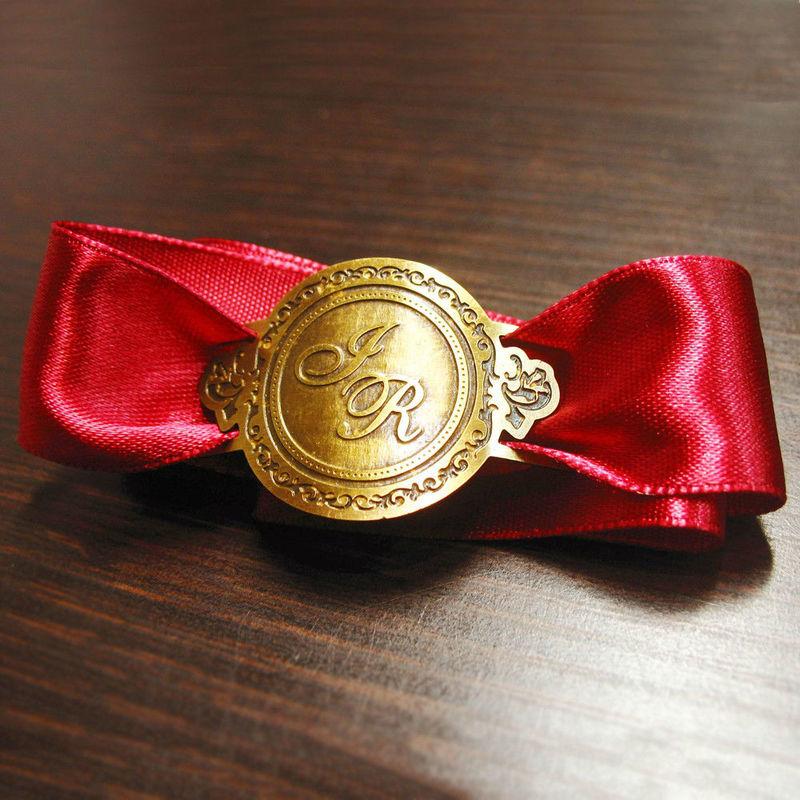 Porta-guardanapo com monograma dos noivos e fita de cetim.
