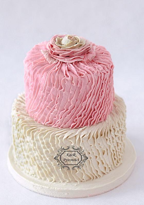 Tort Małej Elegantki. Cały w falbanach, popielato-różowy. Delikatny, waniliowy z wyczuwalną cytrynową nutą.   Klasyczny biały biszkopt, dużo lemon curdu i kremu maślanego na bazie bezy szwajcarskiej.