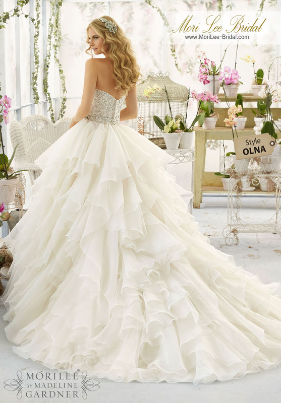 """Dress Style OLNA Intricate Crystal Beaded And Embroidered Bodice Onto a Flounced Organza Skirt  Removable Beaded Satin Belt. Available in Three Lengths: 55"""", 58"""", 61"""". Colors available: White/Silver, Ivory/Silver, Ivory/Light Gold/Silver, Ivory/Blush/Silver."""