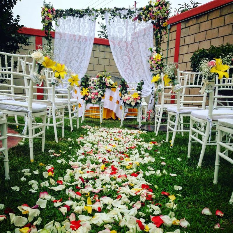 Boda Civil en jardín llena de flores de colores , un camino de pétalos para la novia, sillas decoradas con guirnaldas de flores y de fondo principal un cortinero con medallones en la misma gama de tonos.