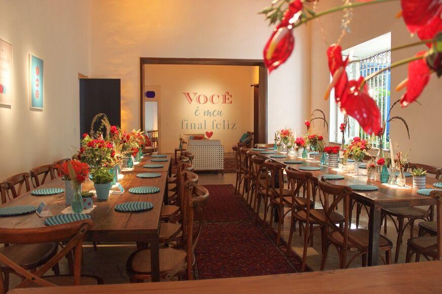 Mesa comunitária para os convidados, com o azul e vermelho em destaque.