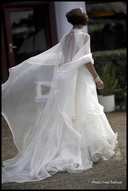 SOPHIE C'est une robe de mariage délicate et romantique.  Elle est confectionnée avec une base soie doupionnée, des organzas de soie, gazar de soie lisse et froissé harmonisées dans les vagues de la robe agrémentée de cristaux Swarovski . Les finitions particulières ourlets ondulés (un clin d'œil aux vagues de l'océan) subliment les effets de mouvements des tissus dans le vent.  Vous étiez merveilleuse Sophie, sublime de douceur et de bonheur. Modèle réalisé avec la collaboration de Lolita pour LEA MADELEINE Couture. Ce modèle a été dessiné par la cliente Sophie. Le photographe est Yves Samuel.