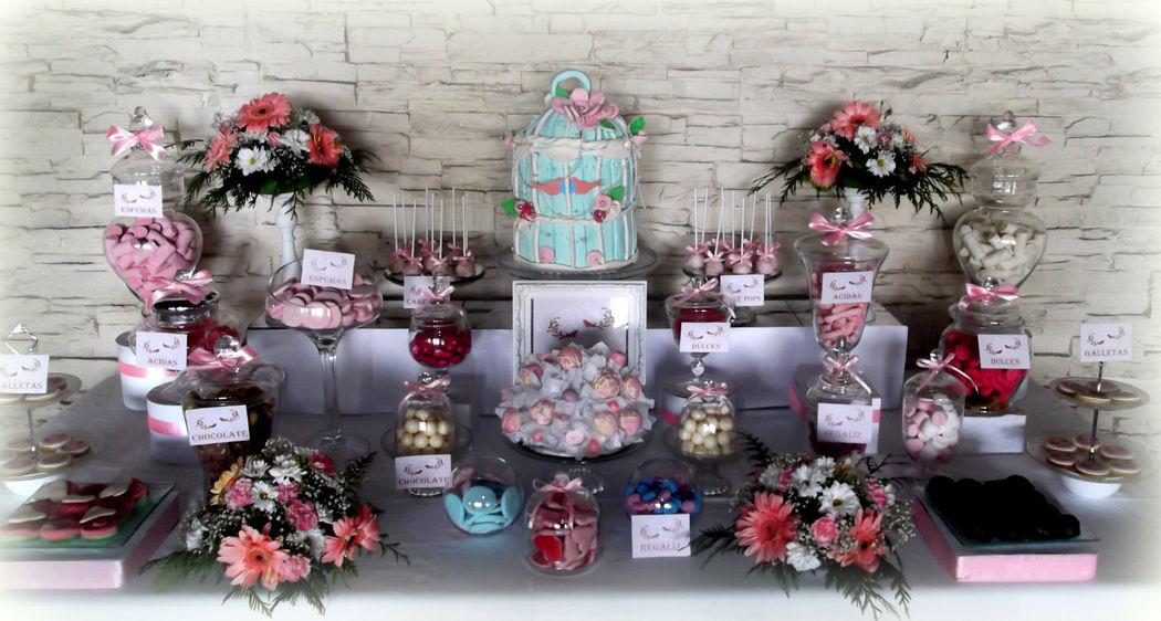 Candy bar en blanco y rosa. La jaula esta elaborada con golosinas.