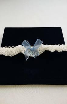 Kiss The Bride, Liga angosta en blonda recogida y decorada con elástico en moritas, con lazo azul en cinta de agua infaltable en una novia.