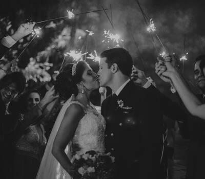 Noivos se beijando e os padrinhos segurando sparkles