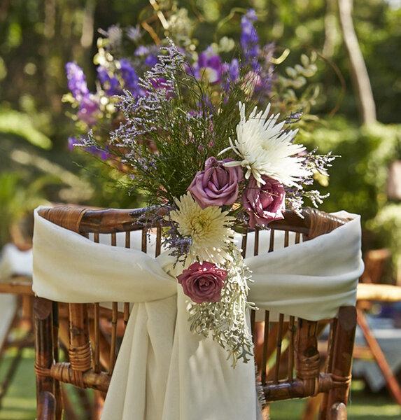 Flores e tecido na decoração da cadeira de casamento.