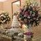 Mesa de bolo e doces com grandes arranjos florais.