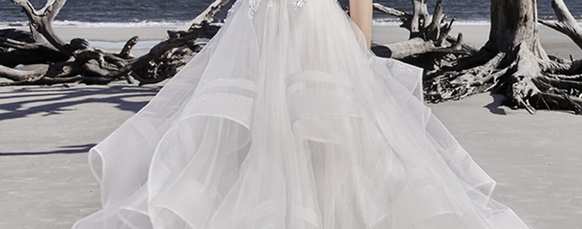 """This modern princess ballgown features a beaded lace bodice, accented in Swarovski crystals, atop a tiered tulle skirt trimmed in horsehair. Beaded lace motifs complete the unique illusion jewel neckline and statement illusion back. Finished with crystal buttons and zipper closure.  <a href=""""https://www.maggiesottero.com/sottero-and-midgley/ariya/11516"""">Sottero and Midgley</a>"""