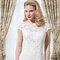 Figurbetontes Brautkleid aus Spitze mit transparentem Dekolleté und kurzen Ärmeln.