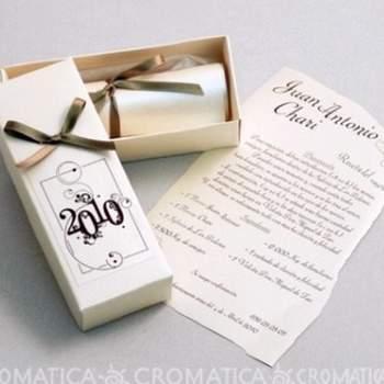 Caja rectangular de color blanco, moño de color en la tapa de la caja, al interior una hoja tipo pergamino enrollada y cerrada con moño del mismo color del exterior.