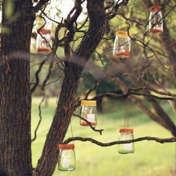 De los árboles se pueden colgar tarros de cristal con velas.