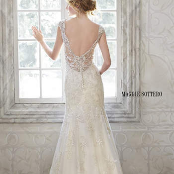 "This delicate, feminine gown features exquisite sequin embroidered lace with shimmer metallic threading and plunging illusion back. Stunning Swarovski crystals and opalescent pearls adorn the illusion cap-sleeves and back of this sheath wedding dress. Complete with crystal button over zipper closure.  <a href=""http://www.maggiesottero.com/dress.aspx?style=5MS077"" target=""_blank"">Maggie Sottero Spring 2015</a>"