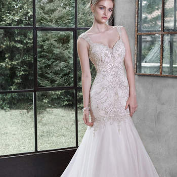 "Glittering Swarovski crystals, shimmering pearls and sparkling sequins adorn the intricate bodice of this Chic organza fit and flare wedding dress, softly falling into a flared skirt. Finished with dramatic sweetheart neckline, deep scoop back and crystal buttons over zipper and inner elastic closure.  <a href=""http://www.maggiesottero.com/dress.aspx?style=5MT652"" target=""_blank"">Maggie Sottero</a>"