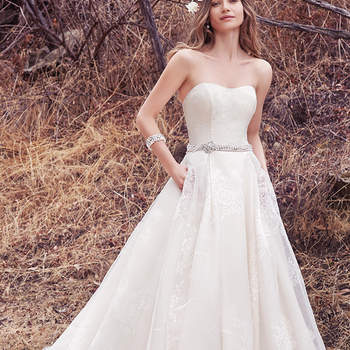 This sweet and elegant ballgown features layers of Vega Organza. A strapless scoop neckline and sheer pockets complete the ethereal romance of this look. Finished with pearl buttons over zipper and inner elastic closure. Pearl and Swarovski crystal belt featuring beaded brooch sold separately.